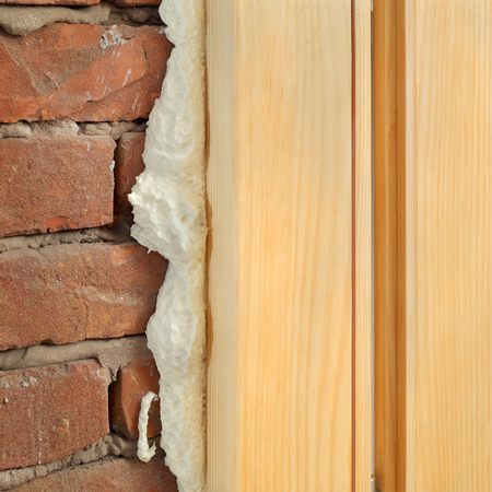 polyurethane: Wooden door or window install, closeup of polyurethane foam wood and bricks Stock Photo