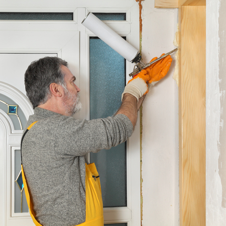 polyurethane: Worker install wooden door, using polyurethane foam to fix it at wall, home renovation