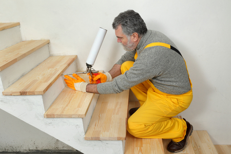 polyurethane: Construction worker fixing wooden stairs with polyurethane spray gun, home renovation Stock Photo