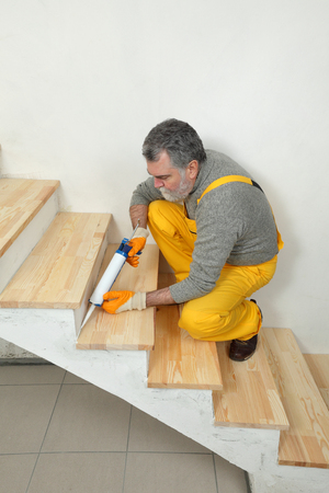 caulk: Construction worker caulking wooden stairs with silicone glue using cartridge, home renovation Stock Photo