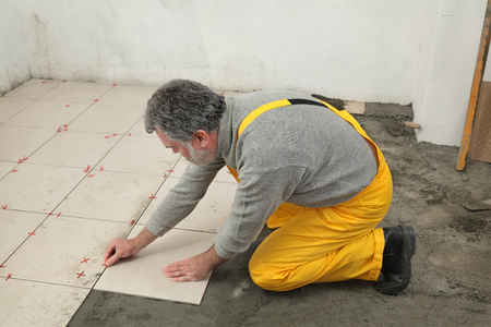 tile adhesive: Home renovation, worker placing tiles to floor, using cement mixed with sand
