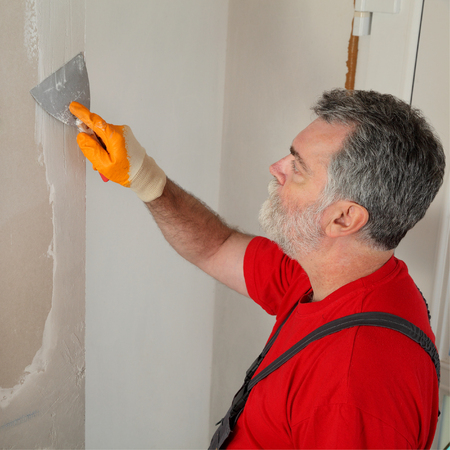 plaster board: Worker spreading plaster with trowel to gypsum board and fiber mesh