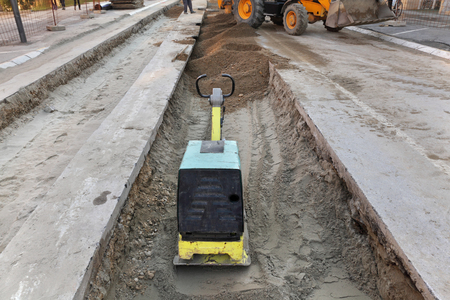 compacting: Vibratory plate compactor compacting sand at road construction site Stock Photo
