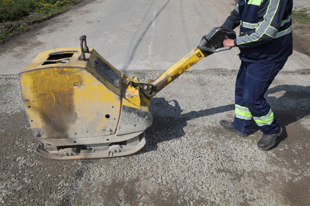 jack tar: Worker use vibratory plate compactor compacting gravel at road construction site Stock Photo