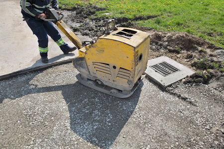 compacting: Worker use vibratory plate compactor compacting gravel at road construction site Stock Photo