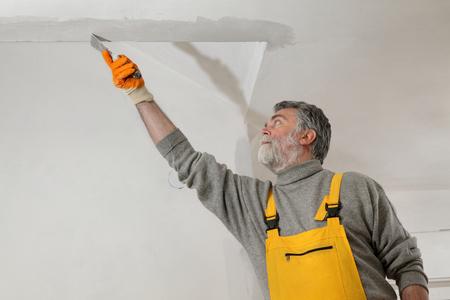 batten: Worker spreading  plaster to wall, corner protecting batten install, repairing works