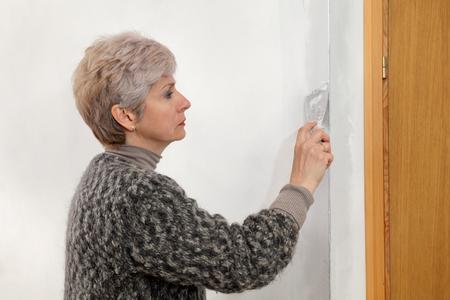 batten: Female worker spreading  plaster to wall, corner protecting batten install, repairing works