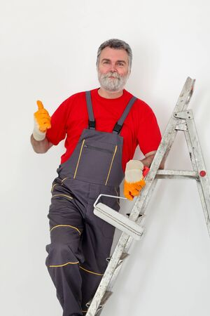 redecoration: Worker painting wall to white and gesturing, with ladder and paint roller