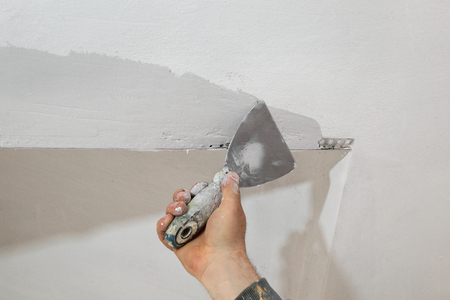 parget: Worker spreading  plaster to wall, corner protecting batten install, repairing works