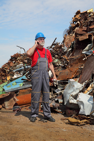 destruct: Metal recycling, worker speaking by mobile phone side by heap of scrap metal Stock Photo