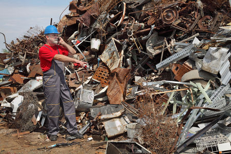 scrap heap: Metal recycling, worker speaking by mobile phone and pointing to heap of scrap metal Stock Photo