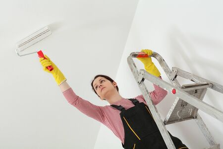 redecoration: Female worker painting ceiling with paint roller from ladder