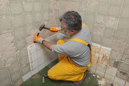 Adult worker remove, demolish old tiles in a bathroom with hammer and chisel Imagens