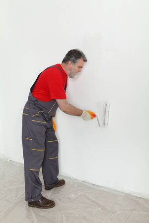 redecoration: Worker painting wall to white with paint roller