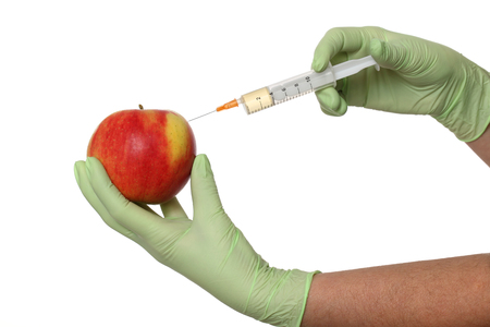 Scientist injecting liquid to red apple using syringe Stock Photo