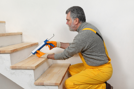 Construction worker caulking wooden stairs with silicone glue using cartridge, home renovation Stok Fotoğraf