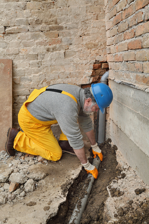 sewerage: Home renovation, plumber fixing sewerage pipe at construction site