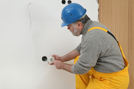 electrical equipment: Electrician installing electrical plug at wall and using voltage testing screwdriver