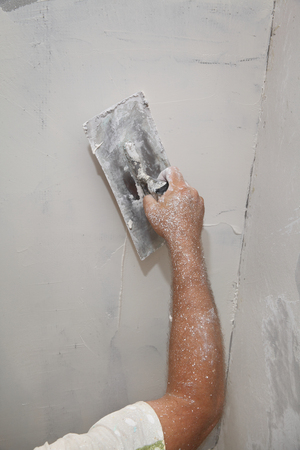 parget: Worker spreading  plaster to wall, repairing works