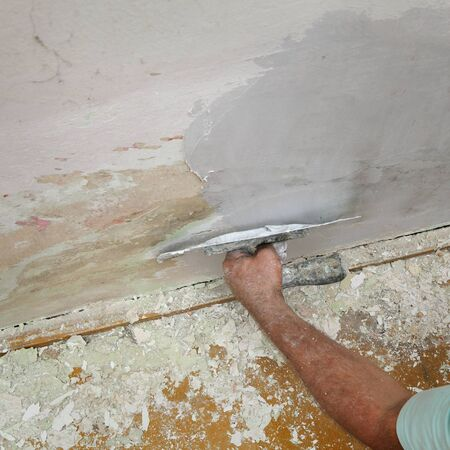 parget: Worker spreading  plaster to damaged wall, repairing works