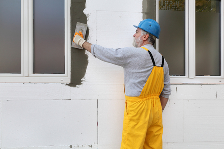 mesh: Worker spreading  mortar over polystyrene wall insulation with trowel Stock Photo