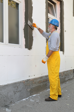 polystyrene: Worker spreading  mortar over polystyrene wall insulation with trowel Stock Photo