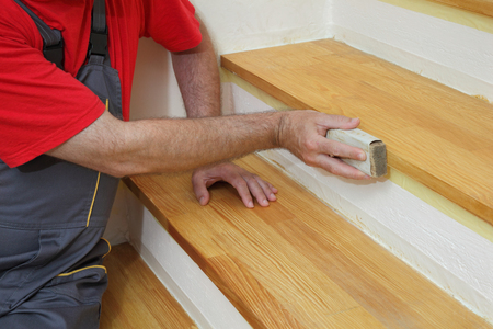wooden stairs: Worker sanding plank at stairs using sand paper, home renovation