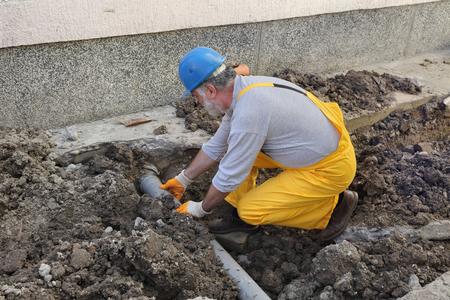 La rénovation domiciliaire, plombier fixation tuyau d'évacuation des eaux usées sur le site de construction