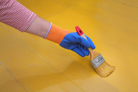 brush painting: Painting of wooden floor, workers hand and brush Stock Photo