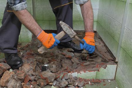 demolition: Worker remove, demolish old bathtub and tiles with hammer and chisel in a bathroom