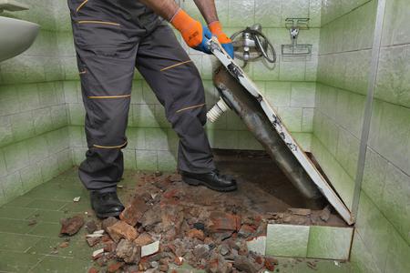 bathroom tiles: Worker remove, demolish old bathtub and tiles in a bathroom