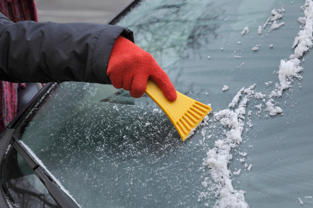 Winter scene, human hand in glove scraping ice from windshield of car