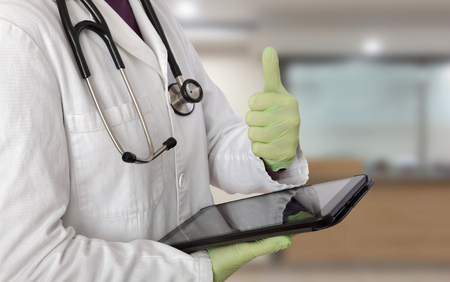 Doctor gesturing with thumb up and with tablet in other hand