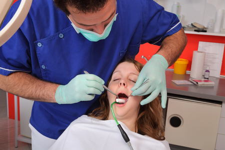 Dentist  putting dental roll to patient mouth photo