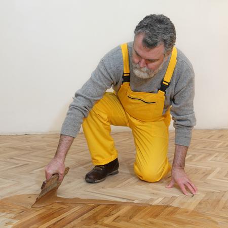 treated board: Varnishing of oak parquet floor, mature adult worker using tool