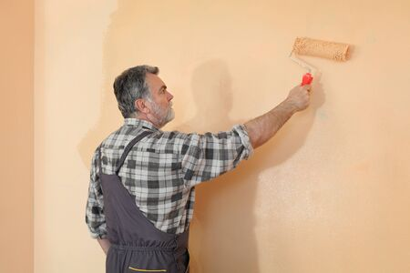 home decorating: Worker painting wall in a room to orange color using paint roller