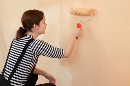 home decorating: Female worker painting wall to orange with paint roller Stock Photo