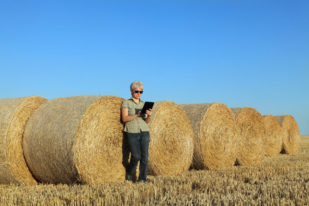 Female farmer in wheat field after harvest examining bale, rolled straw, using tablet photo