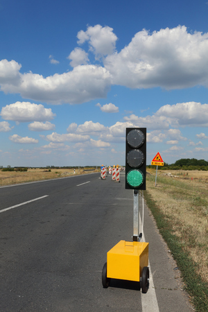 Roadworks, traffic light and road signs at a highway on reconstruction with blue sky and clouds Stock Photo