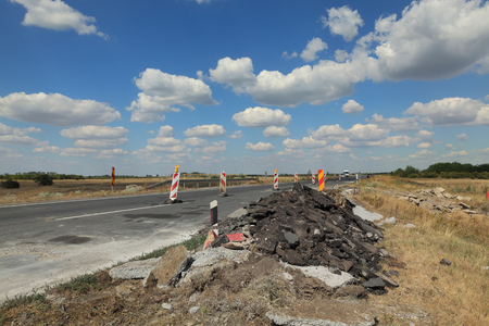 Roadworks, road signs at a highway on reconstruction with blue sky and clouds