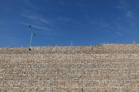 Road embankment of gravel reinforced with steel mesh used for highway in Greece