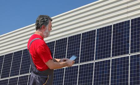 엔지니어 또는 작업자가 백그라운드에서 태양 전지판이있는 태블릿을 사용하여 에너지 절약을 계산합니다.