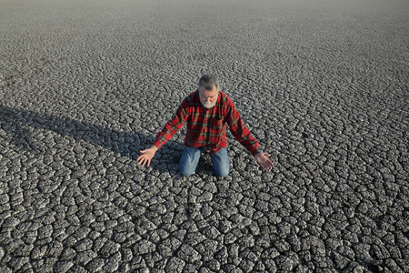 Desperate man kneeling at dry cracked land after drought, natural disaster Foto de archivo