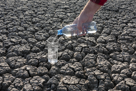 Human hand pouring clear drinking water to glass from bottle on dry cracked land