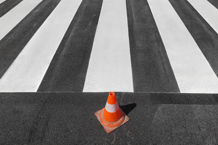 Fresh painted  pedestrian crosswalk at a street with traffic cone Stock Photo