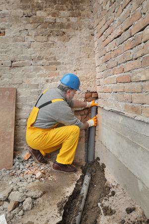 Huisvernieuwing, loodgieter het bevestigen rioleringspijp bij bouwwerf Stockfoto