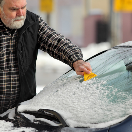 Driver cleaning snow from windshield og car using scraper