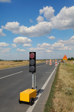 Roadworks, traffic light and road signs at a highway or road on reconstruction with blue sky and clouds