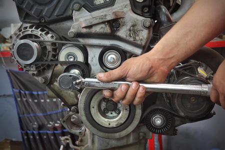 現代の車のエンジンでPKベルト、滑車およびオルタネーターを固定する労働者、手および用具のクローズアップ