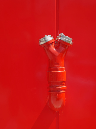 New red fire hydrant at wall of building Stock Photo